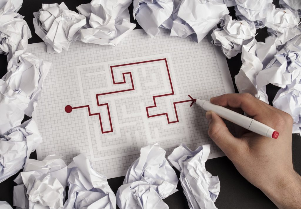 Hand drawing a path through a maze for a business exit strategy